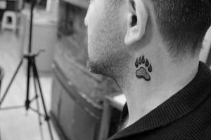 A minimalist tattoo of a paw on the side of the neck