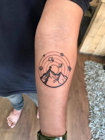 A minimalism tattoo of a landscape and night sky featuring the planets and dotwork