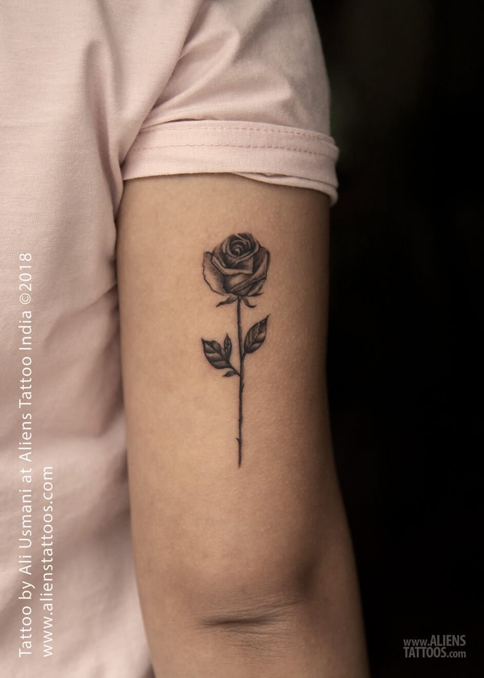 A minimalist blackwork tattoo of a black rose